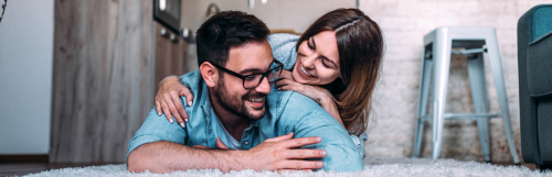 woman lies on man back talking enjoying happy moments together on white fluffy carpet