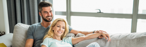 couple sitting on white coach smiling hand in hand in living room