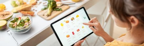 woman shopping online for healthy fruits beside healthy vegetables bowl broccoli on chopping board on table