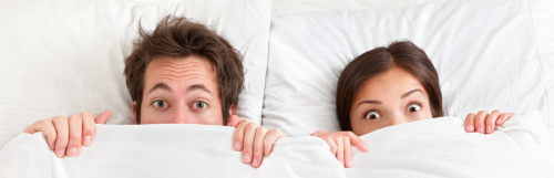 couple lies on white pillows starring covering face with big white blanket