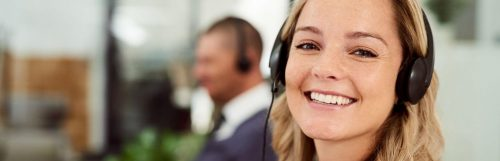 woman happily smiles wearing headphone sits in office