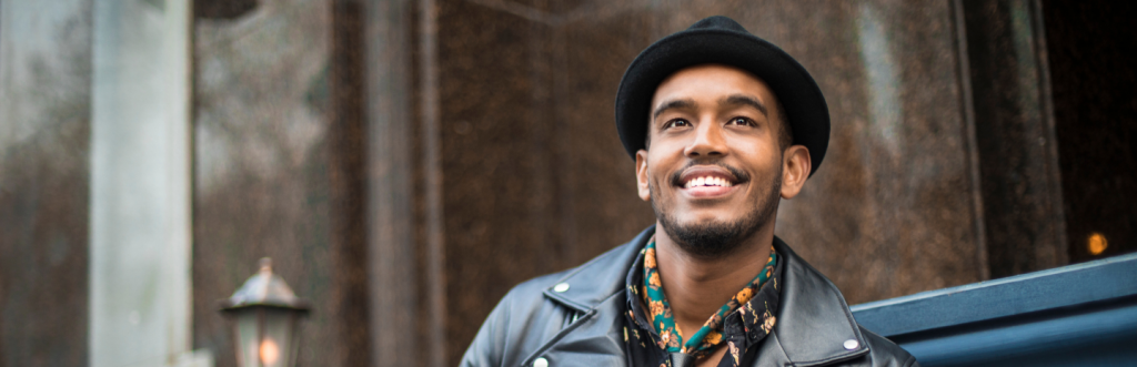 happy man with black fedora dark blue jacket stands alone smiling