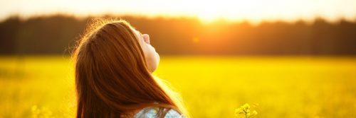 young woman heads up enjoying sunlight nature in canola field