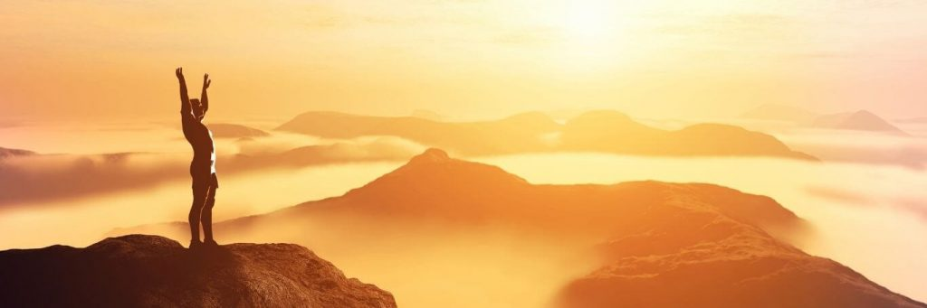 person stood on top of mountain raises hand gratitude life in beautiful foggy sunny weather