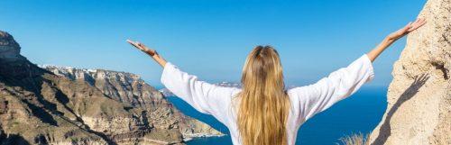 woman gratitude earth blue ocean sky white shirt blonde coast rocks