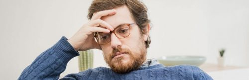 man hand on forehead wistful eyes sits in living room worrying thinking about his emotions
