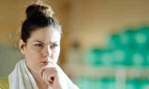 woman irritated face looks at herself in mirror