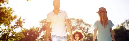 parents little adorable daughter holds hand walking happily in park in beautiful sunny weather