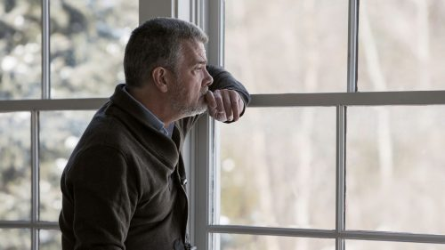 uncertain man looking out window thinking contemplate inside looking outside