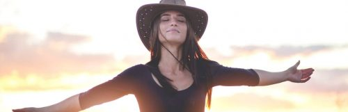 woman wears hat eyes closed gratitude life in sunset