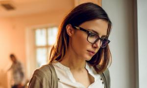 business woman wears black frame prescription glasses focuses on work in quiet office