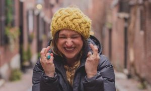 excited woman with yellow beanie and dark blue winter coat stands alone between two arrays of buildings