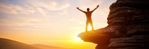 man stood on rock celebrated in beautiful sunset