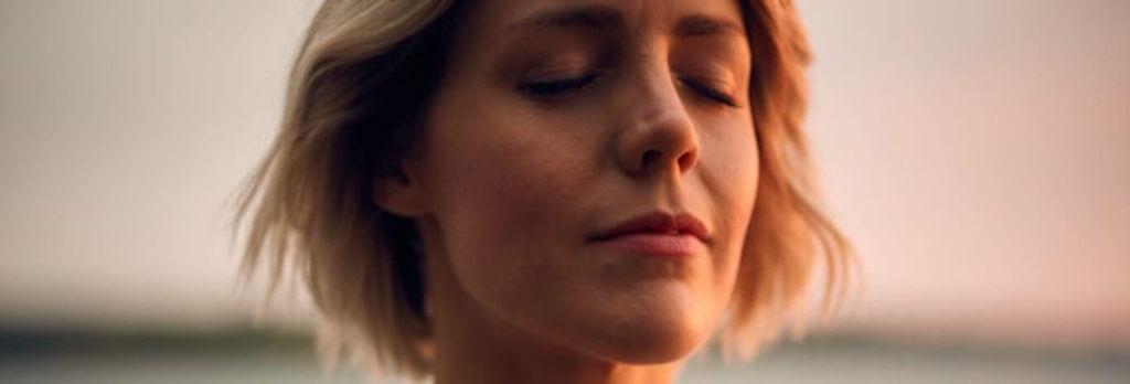 short hair woman eyes closed focuses on breathing meditation