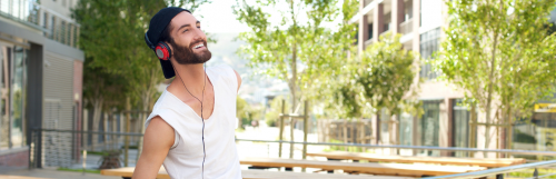 man with white sleeveless shirt wears headphone smiles looks at sky in quiet park