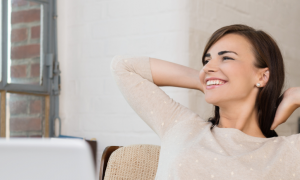 young woman sits alone in office smiles looks outside window