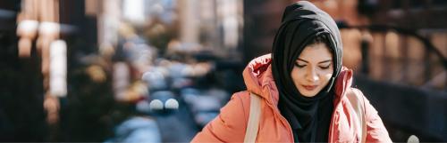 woman wears black hoodie and light pink raincoat face down walks alone