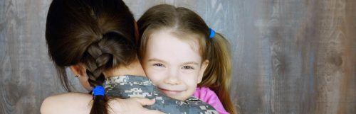 daughter hair tied with blue band happily smiles hugs mom