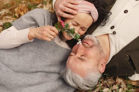 elderly couple happily smiles talks as man hands on lady head