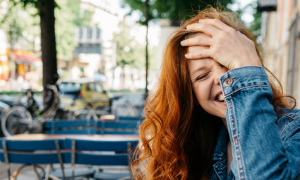 long curly brown hair woman with happy face hand on forehead laughs standing next to restaurant