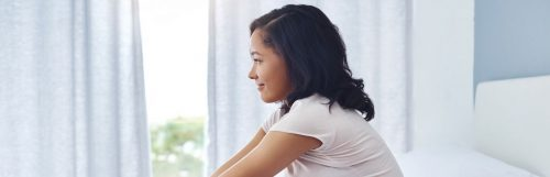 young woman sitting on bed looking through window happily smiling