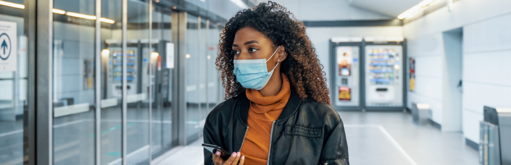 long curly brown hair woman wears face mask hand holding phone looks for store