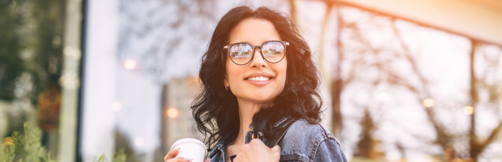 long curly black hair lady happily smiles hand holding white cup