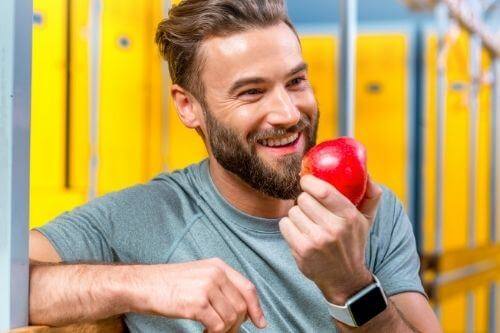 Healthy young man eating a delicious red apple