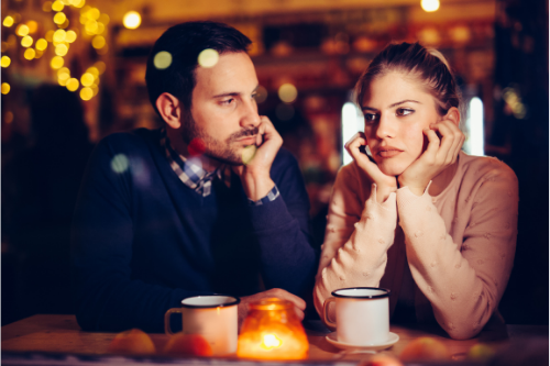 couple sitting at coffee shop with orange ambient candle looking frustrated