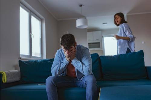 man sitting on blue couch face in hand crying  as woman yells angrily from across room