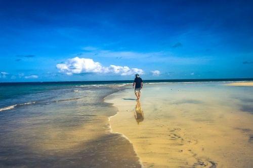 Man being present walking along the beach.