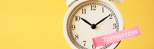 creamy colored clock points at ten ten o clock indicating procrastinating and leaving work for tomorrow