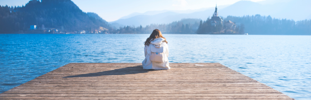 white hoodie girl sits alone facing blue ocean in quiet mountainous area