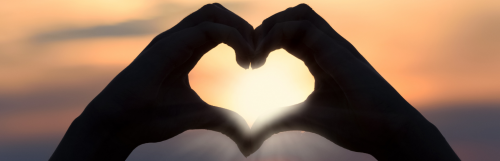 two hands heart shape in beautiful sunset background