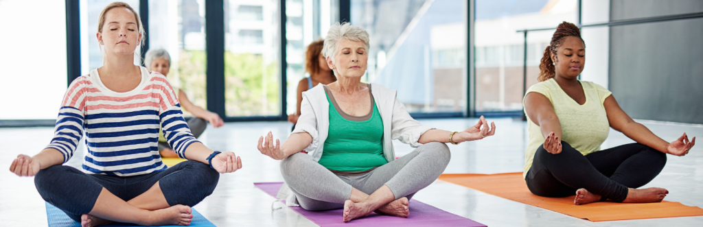 group of five ladies with different ages sit leg crossed meditate peacefully