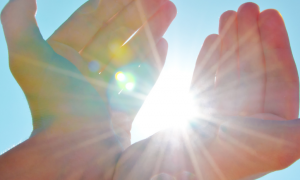 two hands cover sunlight in clear blue sky
