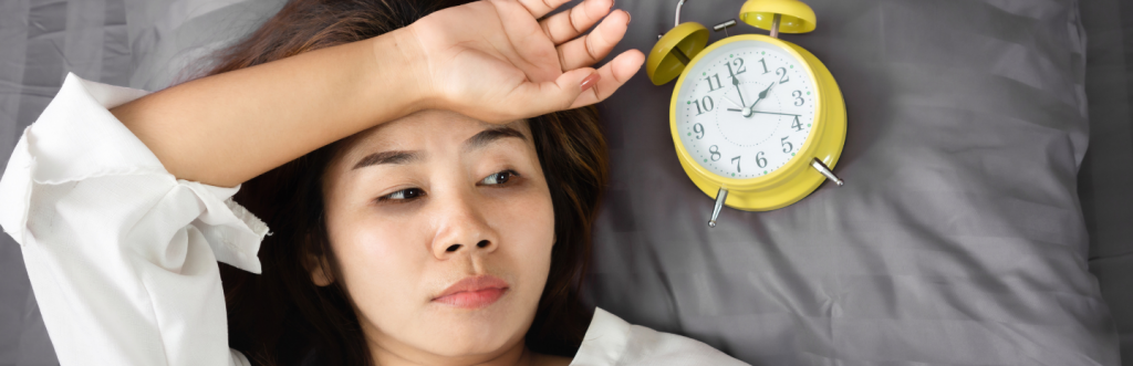 young girl puts hand on forehead worries thinks next to yellow clock indicating two o clock