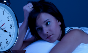 woman lies on bed scratches hair looks at clock at late night
