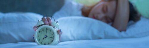Girl hand on head holds white clock sleeps beside white pillows