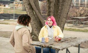 short straight pink hair girl wear yellow jacket talk to short curly hair lady facing backward in park