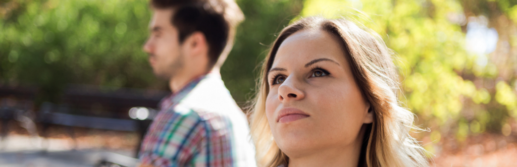 couple sits in park unhappily not talk to each other has conflict in sunny sky