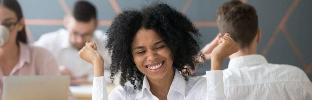 woman of colour celebrating success professional white shirt