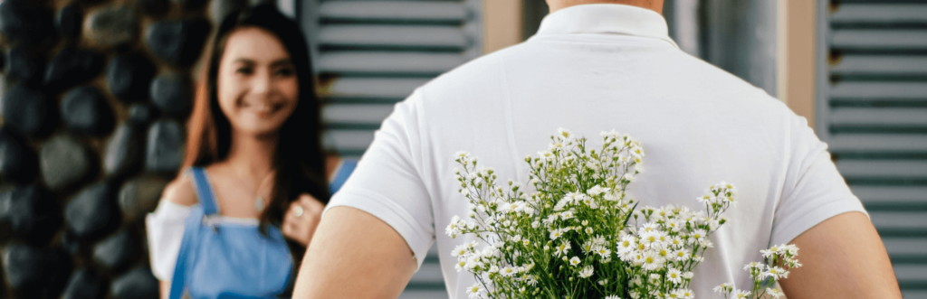 young woman stands in front of gate smiles at man wearing white t shirt hiding flowers behind back