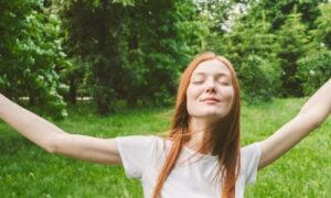 young woman raises hands eyes closed happily enjoys immerses into nature stands in forest
