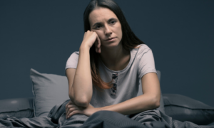 woman hand on face tiredly sits on bed lamps on experiences insomnia