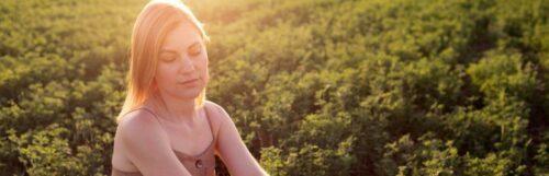 woman looks downward sits on green field in beautiful sunny sky