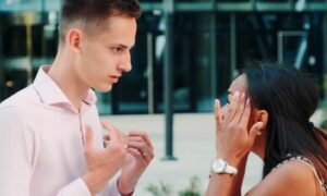 couple stands outside modern office building fights explains to each other