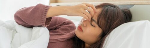 girl with tired face hand on forehead eyes closed lies on bed struggles to fall asleep