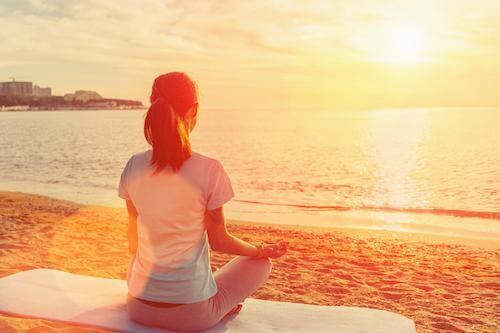 a woman meditating under the sun