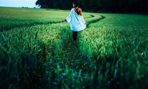 woman walking through grass
